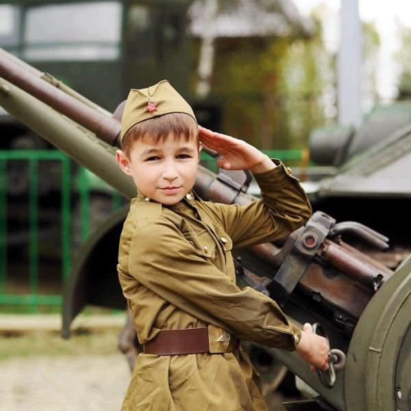 Мальчик в военной форме рядом с пушкой на День Победы