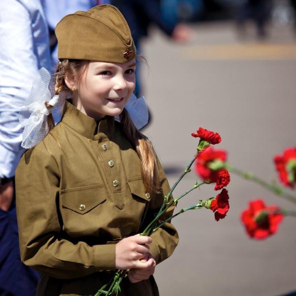 Девочка с цветами в военной форме на День Победы