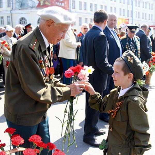 Мальчик дарит цветы ветерану День Победы