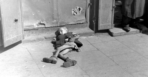 Истощенный ребенок, лежащий на тротуаре в варшавском гетто