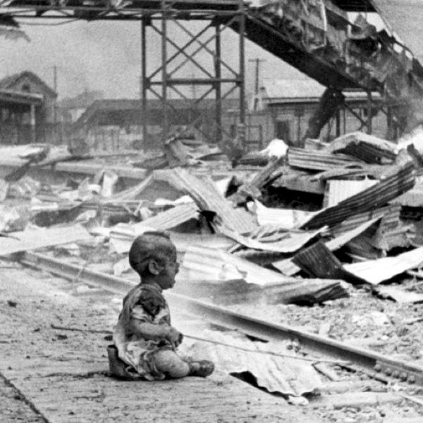 Плачущий китайский ребенок на платформе разбомбленной железнодорожной станции «Юг» в Шанхае