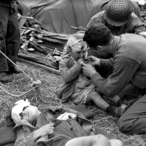 Американские медики и раненая французская девочка Женевьев Мари (Geneviève Marie) в полевом госпитале на ферме Ла Усе (La Houssaye).