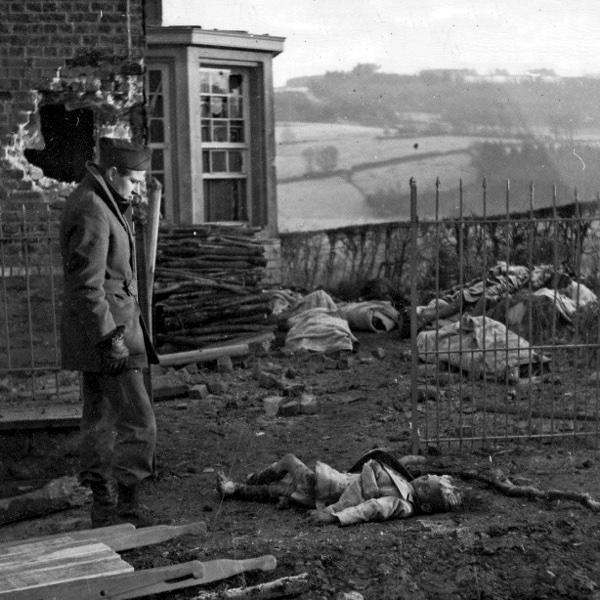 Американский солдат у тела убитого немцами в Ставело (Stavelot) бельгийского мальчика. На заднем плане видны тела других расстрелянных мирных жителей.